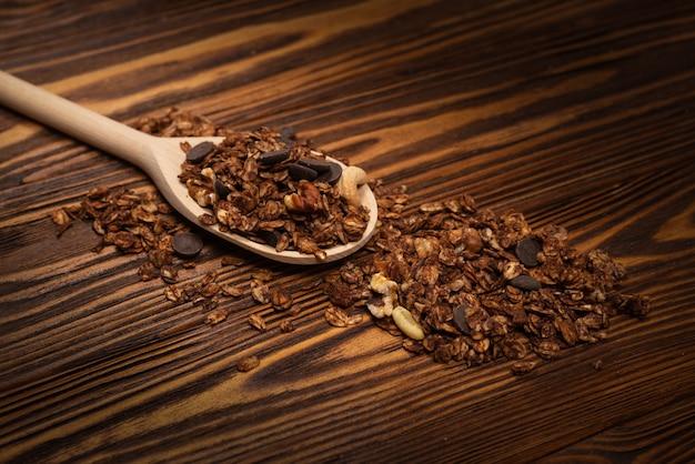 Schokoladen-müsli-müsli mit nüssen in einem holzlöffel. auf einem hölzernen hintergrund.