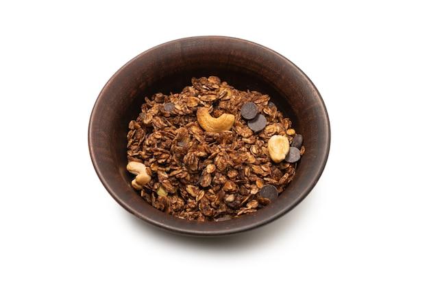 Schokoladen-müsli-müsli mit nüssen in einem schüsselhintergrund. auf weißem grund isoliert.
