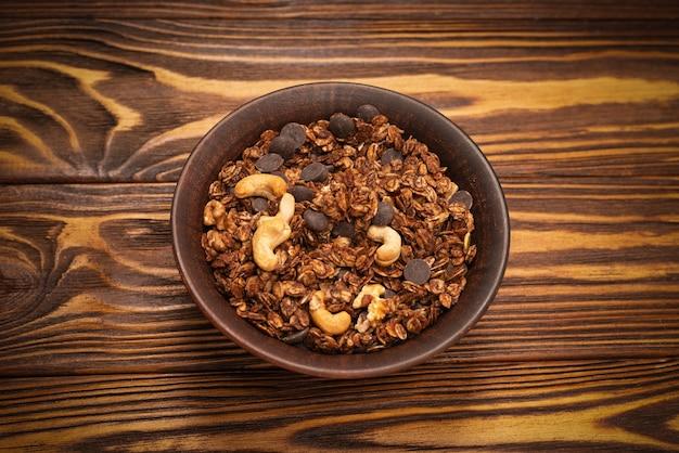 Schokoladen-müsli-müsli mit nüssen in einer schüssel auf einem hölzernen hintergrund.