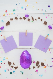 Schokoladen-osterei in folie mit kleinen papieren auf dem tisch