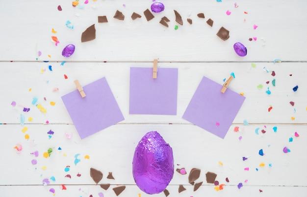 Schokoladen-osterei in folie mit kleinen papieren