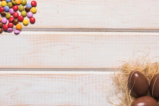 Schokoladen-osterei-nest und edelstein-süßigkeiten an der ecke des hölzernen schreibtisches