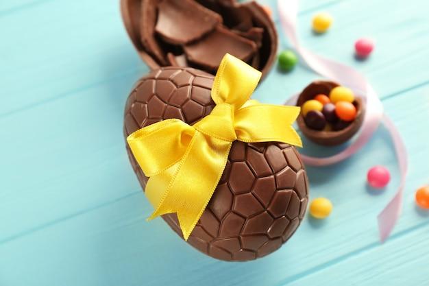 Schokoladen-ostereier auf farbigem holztisch
