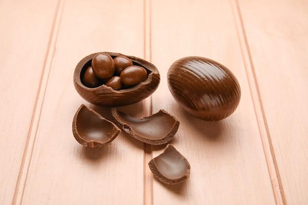 Schokoladen-ostereier auf farbiger holzoberfläche