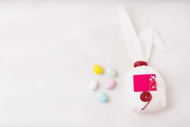 Schokoladen-ostereier glasiert mit pastellfarbe. hasenförmiges weißes backpapier. der platz für den text auf dem papier. frohe ostern konzept. speicherplatz kopieren. draufsicht