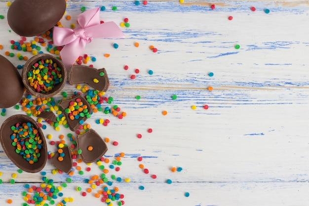 Schokoladen-ostereier, mehrfarbige bonbons auf der weißen holzoberfläche. ostern-konzept. flachgelegt, draufsicht