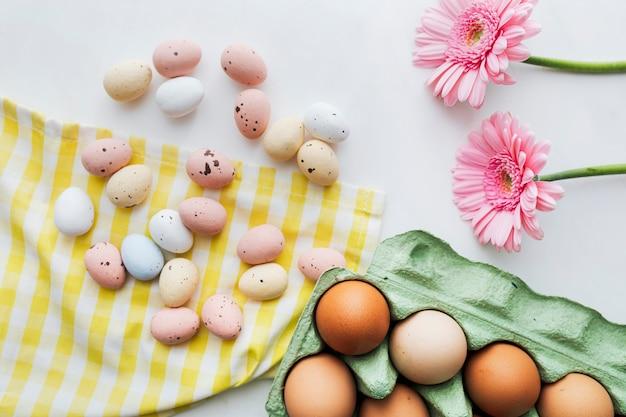 Schokoladen-ostereier und rosa gerbera-blumen flatlay