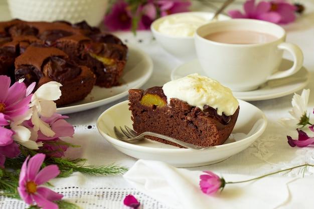 Schokoladen-pflaumenkuchen mit schlagsahne, serviert mit kakao. rustikaler stil.