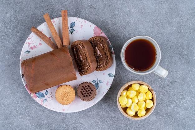 Schokoladen-rollenkuchen mit keksen und heißem tee auf marmoroberfläche