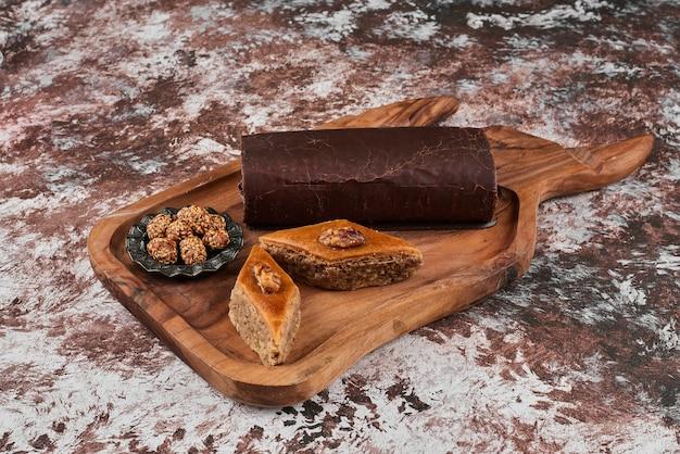 Schokoladen-rollkuchen mit pakhlava auf einem holzbrett.