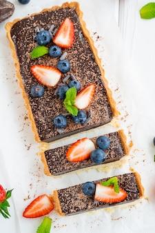 Schokoladen-sahne-torte mit frischen blaubeeren und erdbeeren auf weißem holzhintergrund