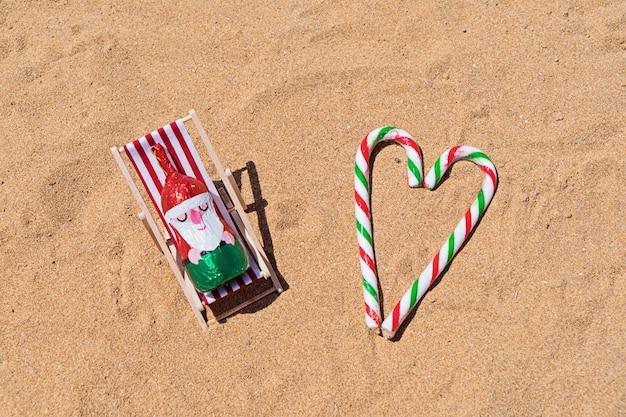 Schokoladen-sankt, die im klappstuhl auf sandigem strand stillsteht