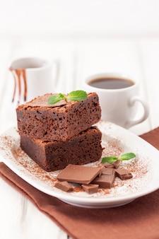 Schokoladen-schokoladenkuchen-quadratstücke im stapel auf der weißen platte verziert mit tadellosen blättern und kakaopulver
