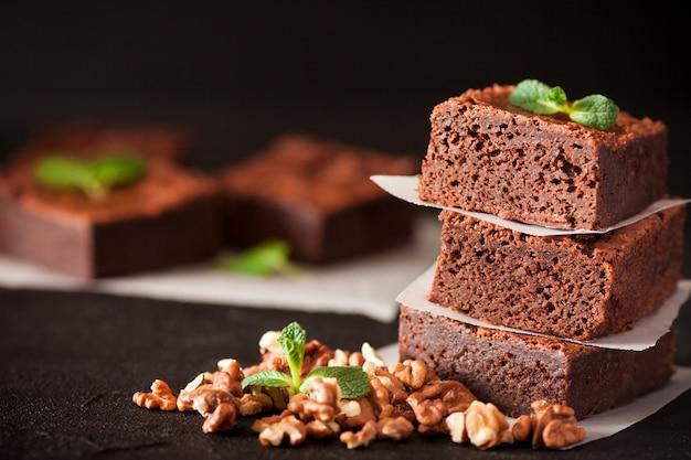 Schokoladen-schokoladenkuchen-quadratstücke im stapel mit walnüssen, tadellosen blättern und kakao