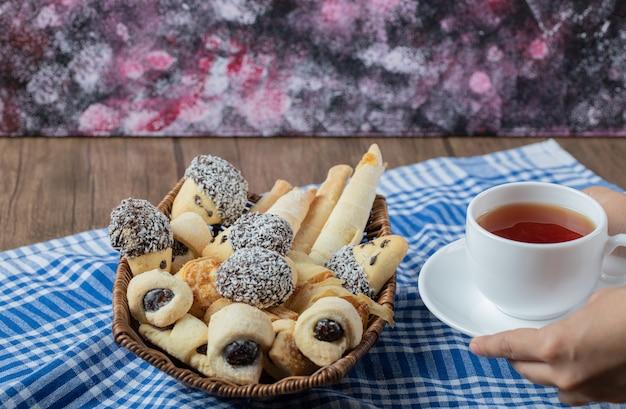 Schokoladen-sesam-kekse in einem holzkorb mit einer tasse earl grey-tee.