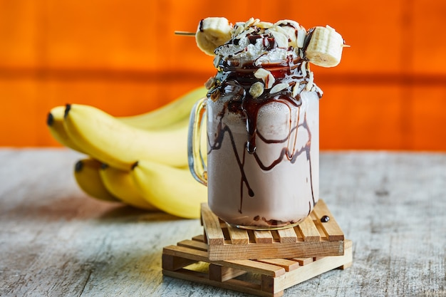 Schokoladen-smoothie mit schokoladensirup und bananenzweig