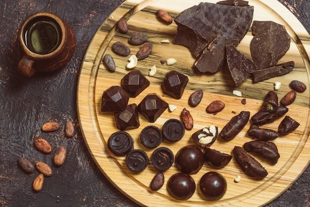 Schokoladen, süßigkeiten, kakaobohnen auf einem holzbrett. süßigkeiten. draufsicht
