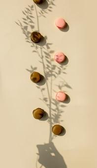 Schokoladen- und erdbeermakronen und trockener blumenzweig auf gelber oberfläche