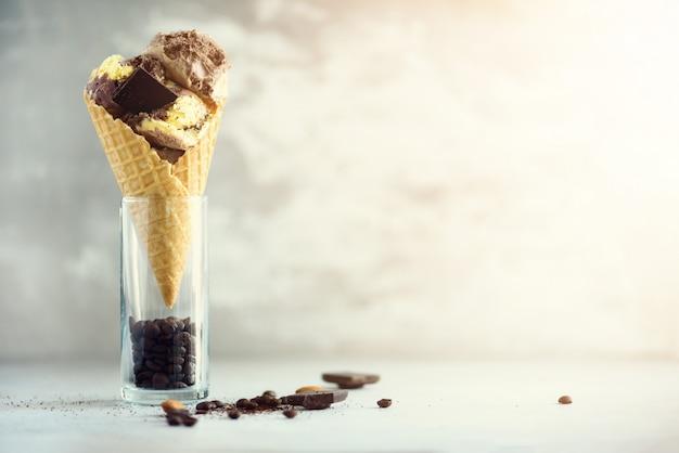 Schokoladen- und kaffeeeiscreme im waffelkegel mit kaffeebohnen auf grauem stein. sommerlebensmittelkonzept, kopienraum. gesundes glutenfreies eis