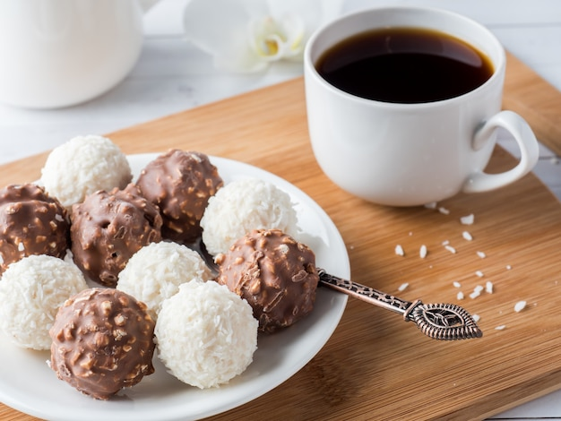 Schokoladen-und kokosnuss-süßigkeiten in einer schüssel auf einer hölzernen behälter kaffeetasse-orchidee
