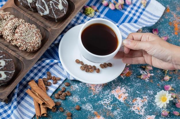 Schokoladen- und kokosplätzchen auf holzbrett serviert mit einer tasse tee.