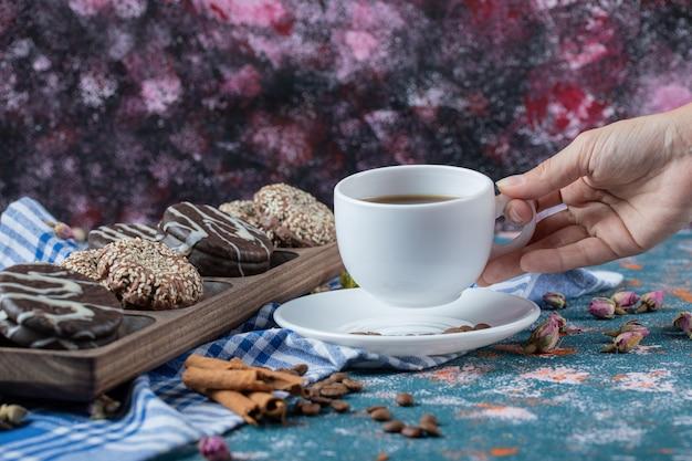 Schokoladen- und sesamplätzchen in einer holzplatte mit einer tasse tee.