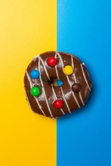 Schokoladen-vanille-donut mit süßigkeiten auf gelb-blauem hintergrund