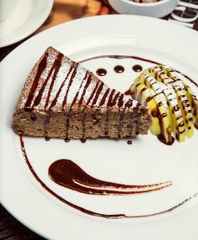 Schokoladenapfelkuchenscheibe mit schokosoße und apfelscheiben.