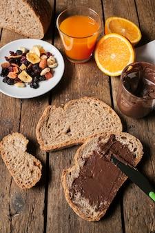 Schokoladenaufstrich auf brotscheibe mit orangensaft