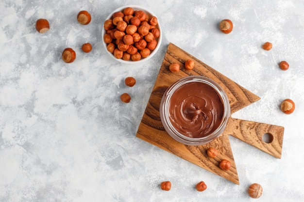 Schokoladenaufstrich oder nugatcreme mit haselnüssen im glasgefäß auf beton, copyspace