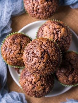 Schokoladenbananenmuffins mit zuckerspitze auf dunkelblauem hintergrund.