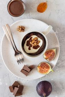 Schokoladenbecherkleiner kuchen mit frischkäse oder ricotta mit karamellsoße in einem weißen keramikbecher. genießen sie herbst- oder wintergerichte.