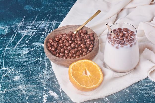 Schokoladenbohnen mit einer tasse milch auf blau.