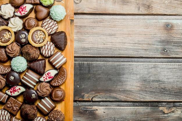 Schokoladenbonbons auf einem holzbrett. auf einem hölzernen hintergrund.