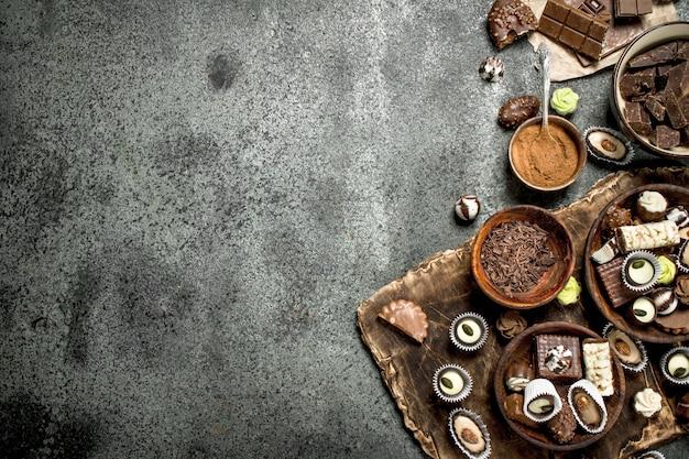 Schokoladenbonbons mit kakaopulver. auf einem rustikalen hintergrund.