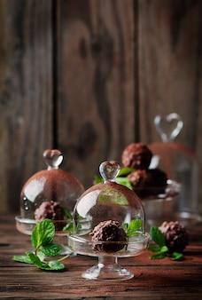 Schokoladenbonbons mit nüssen, minze und kakao auf dem vintage-tisch