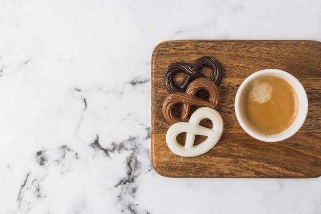 Schokoladenbrezeln und kaffeetasse auf hackendem brett über strukturiertem hintergrund des marmors