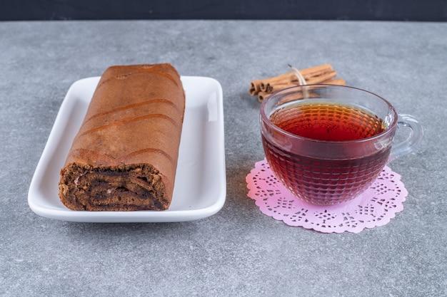 Schokoladenbrötchenkuchen und heißer tee auf marmoroberfläche