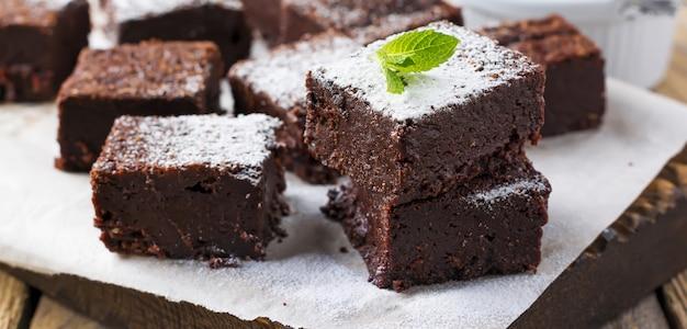 Schokoladenbrownies mit puderzucker und kirschen auf dunklem holzhintergrund. selektiver fokus.