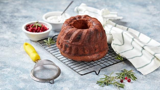 Schokoladenbundt-kuchen auf einem metalldrahtgestell, puderzucker und preiselbeeren in schalen, für die dekoration vorbereitet
