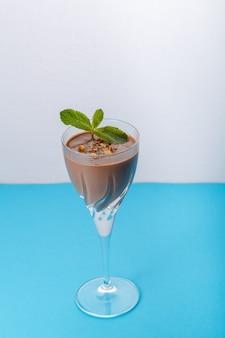 Schokoladencocktail mit nüssen und minze in einem glas auf blauer oberfläche