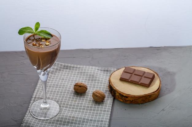 Schokoladencocktail mit nüssen und minze in einem glas auf einer blauen oberfläche in der nähe von nüssen und schokolade auf einer serviette
