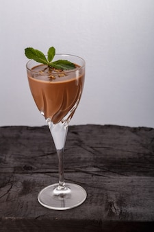 Schokoladencocktail mit nüssen und minze in einem glas auf einer schwarzen oberfläche