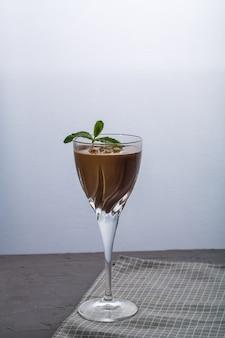 Schokoladencocktail mit nüssen und minze in einem glas auf schwarzem hintergrund. vertikales foto