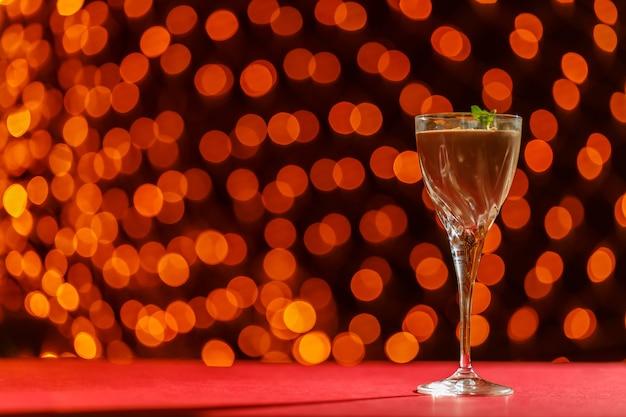 Schokoladencocktail mit nüssen und minze in einem glas gegen eine verschwommene lichteroberfläche