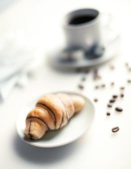 Schokoladencroissant eine tasse kaffee und kaffeebohnen auf weißem tisch geringe schärfentiefe