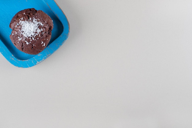 Schokoladencupcake auf einer blauen platte auf marmorhintergrund.
