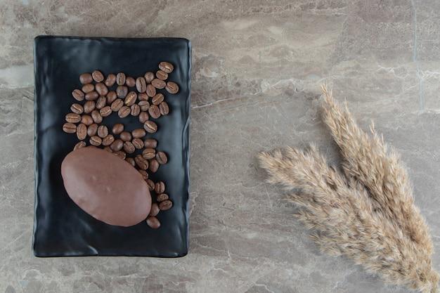Schokoladencupcake auf schwarzem teller mit kaffeebohnen