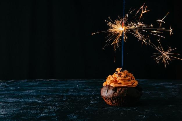 Schokoladencupcake mit sahne und brennender wunderkerze