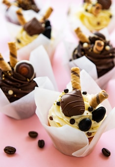 Schokoladencupcakes auf pastellrosa oberfläche
